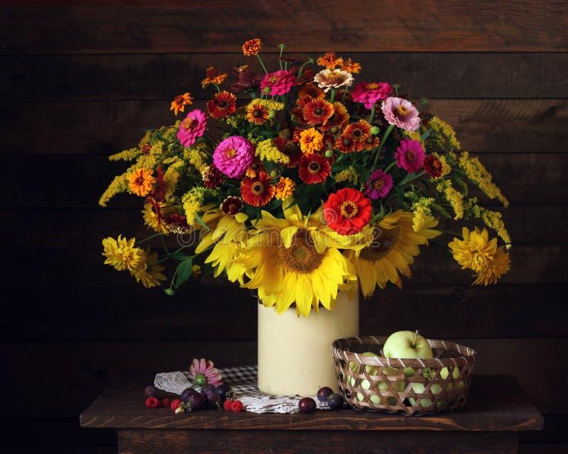 在一个罐头、苹果、莓和李子的花在桌上 库存图片