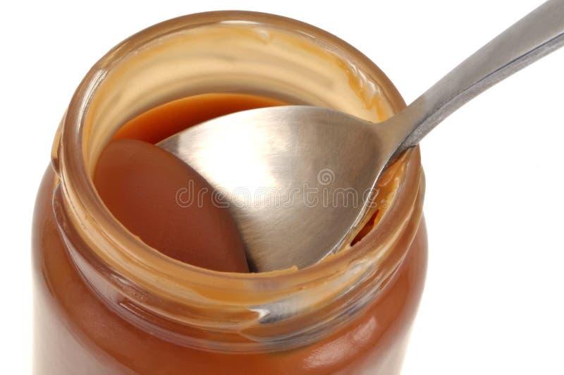 在一个罐的匙子盐味的黄油焦糖 图库摄影