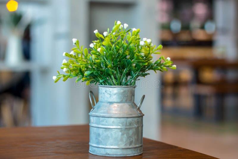 在一个罐的白色塑料花在桌上 免版税库存照片