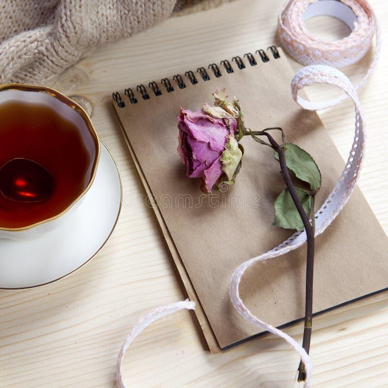 在一个羊毛格子花呢披肩和垫包裹的葡萄酒茶以干燥在桌上上升了 库存图片
