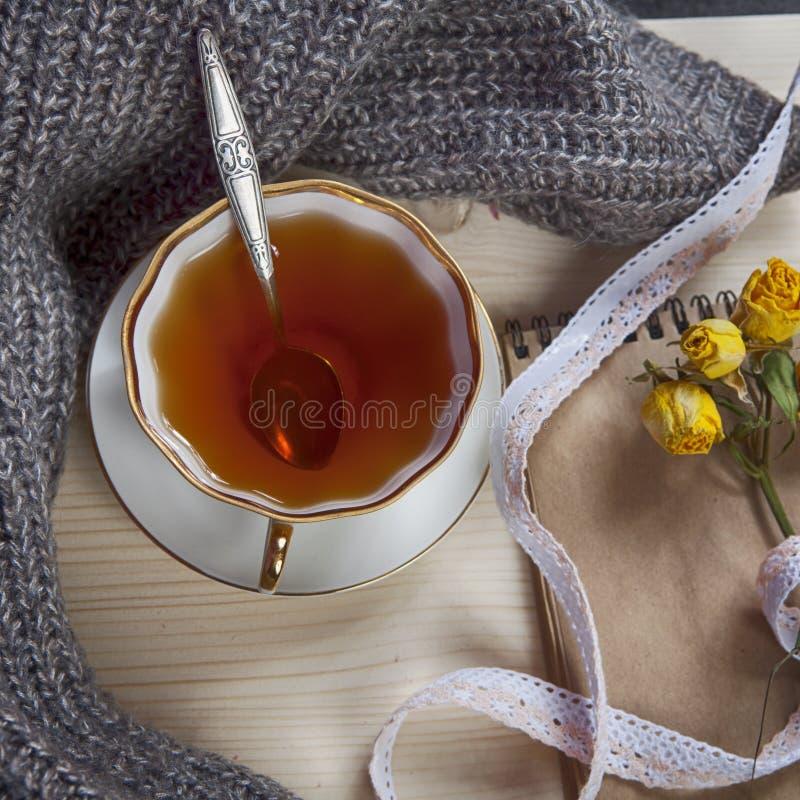 在一个羊毛格子花呢披肩和垫包裹的葡萄酒茶以干燥在桌上上升了 库存照片