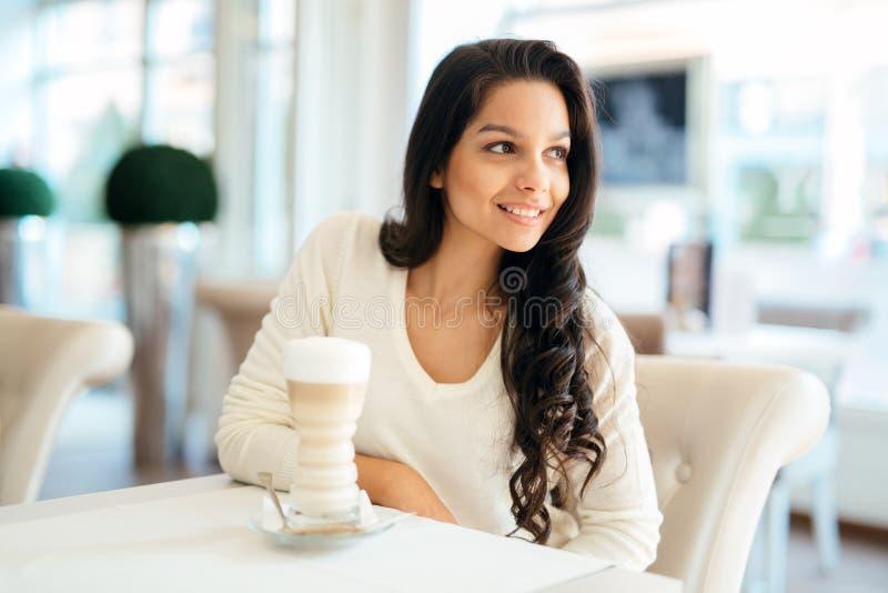 在一个美丽的咖啡馆的迷人的小姐饮用的咖啡 免版税库存照片