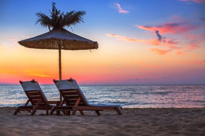在一个美丽的沙滩的生动的日出与遮光罩 库存照片
