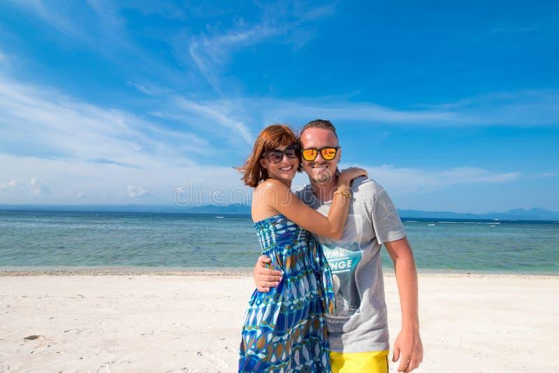 在一个美丽的海滩的愉快的浪漫年轻夫妇与白色沙子 有白种人的夫妇在热带的假期 库存照片