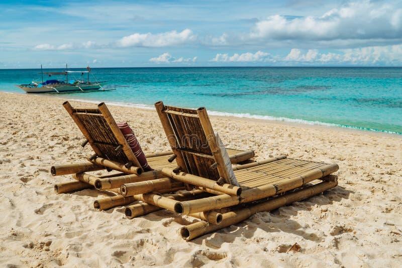 在一个美丽的热带海滩的两把竹椅子与白色沙子和清楚的绿松石海洋 异乎寻常的海岛在菲律宾 库存图片