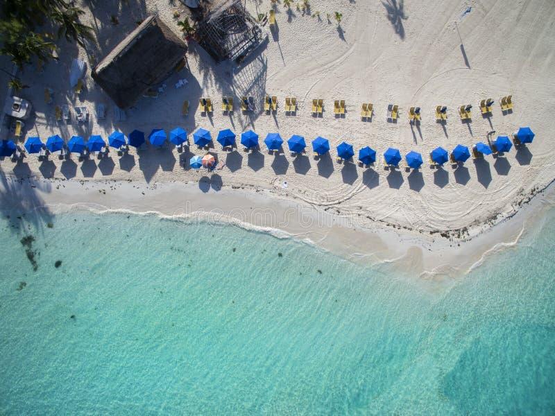 在一个美丽的白色沙子海滩-鸟瞰图的沙滩伞 图库摄影