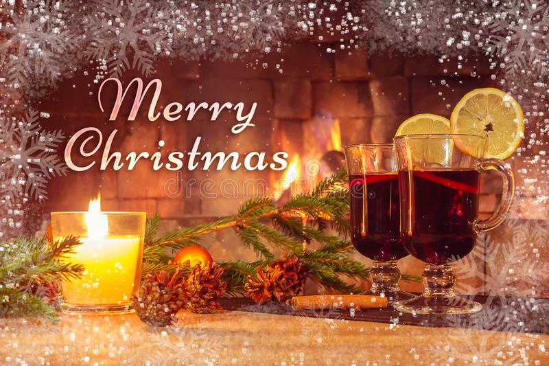 在一个美好的图象的背景的文本圣诞快乐用加香料的热葡萄酒和壁炉 浪漫圣诞卡片 库存照片