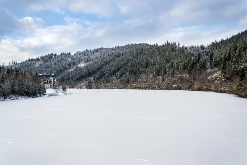 在一个美好的多雪的冬天风景的孤零零旅馆大厦与森林和冻水坝 免版税图库摄影