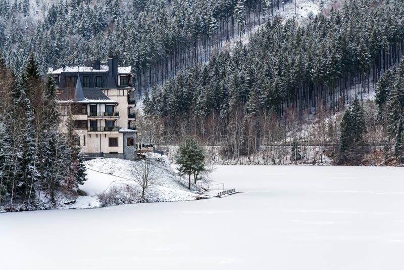 在一个美好的多雪的冬天风景的孤零零旅馆大厦与森林和冻水坝 库存图片
