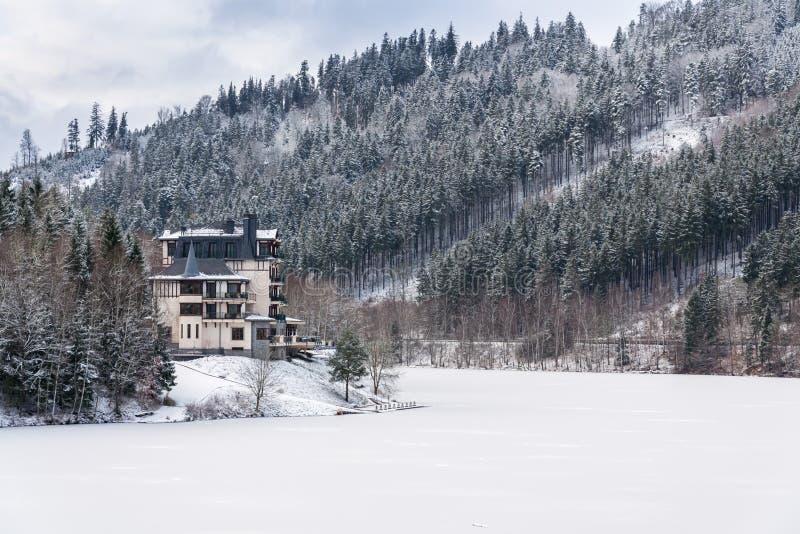 在一个美好的多雪的冬天风景的孤零零旅馆大厦与森林和冻水坝 图库摄影
