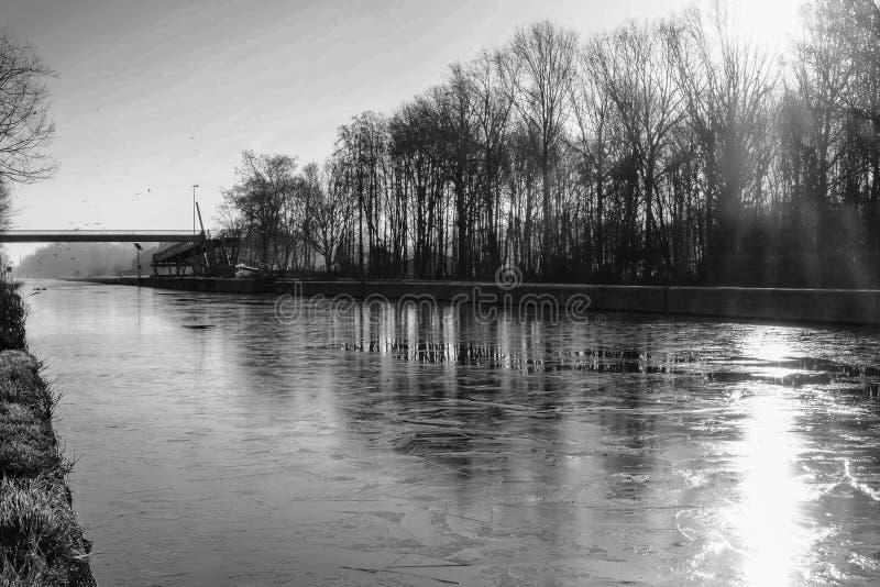 在一个美好的早冬天风景的剧烈和单色日出与一条冻河 免版税图库摄影