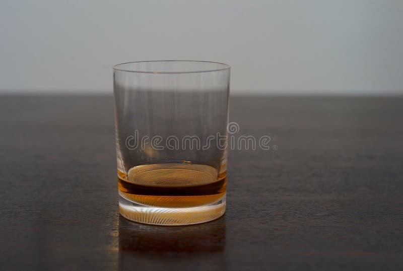 在一个翻转者的威士忌酒在木表上 库存照片