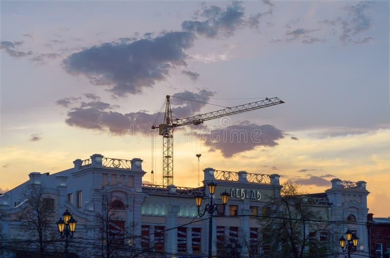 在一个老大厦后的建筑用起重机反对日落天空 库存照片