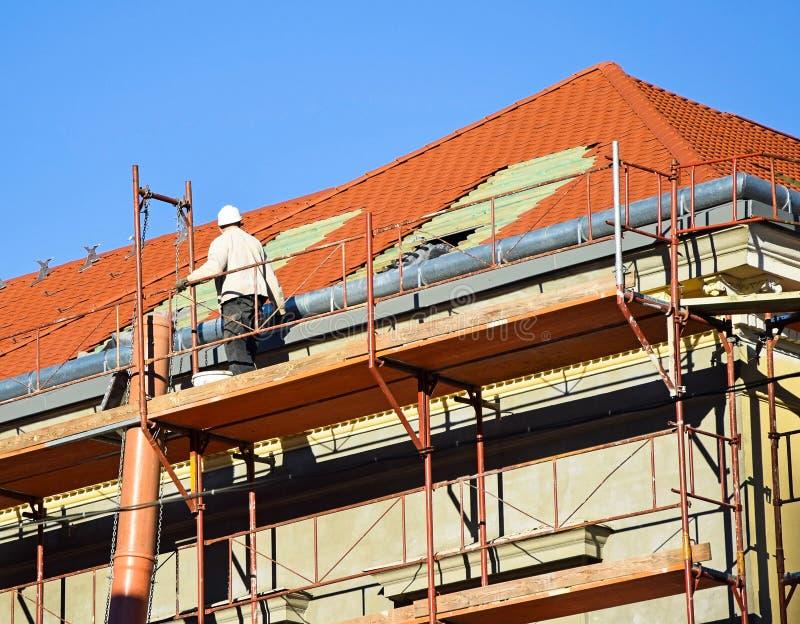 在一个老大厦的屋顶的盖屋顶的人工作 免版税库存图片