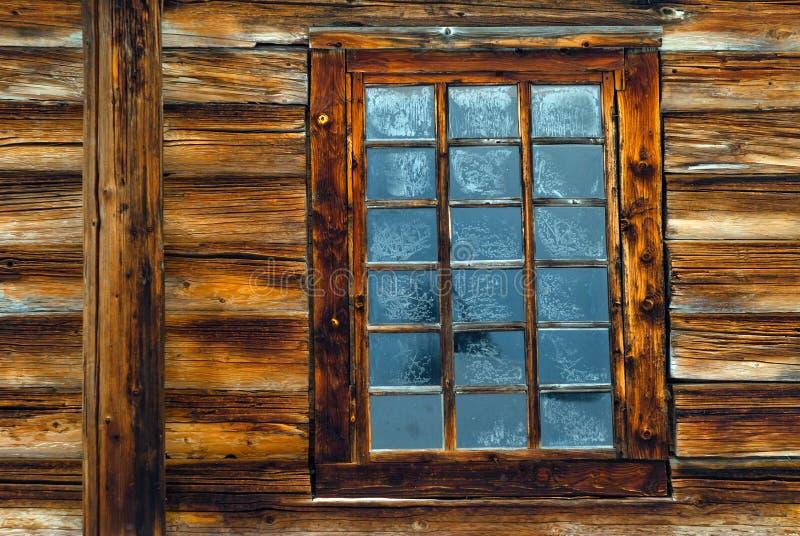 在一个老大厦的日志墙壁的窗口 免版税库存照片