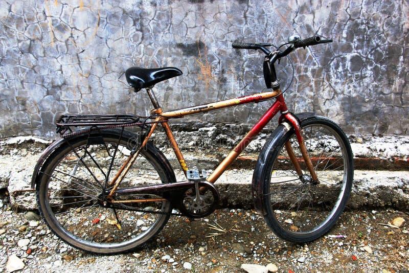 在一个老房子的墙壁的老自行车 免版税库存图片