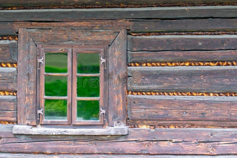 在一个老木房子的墙壁的一个小窗口 库存照片