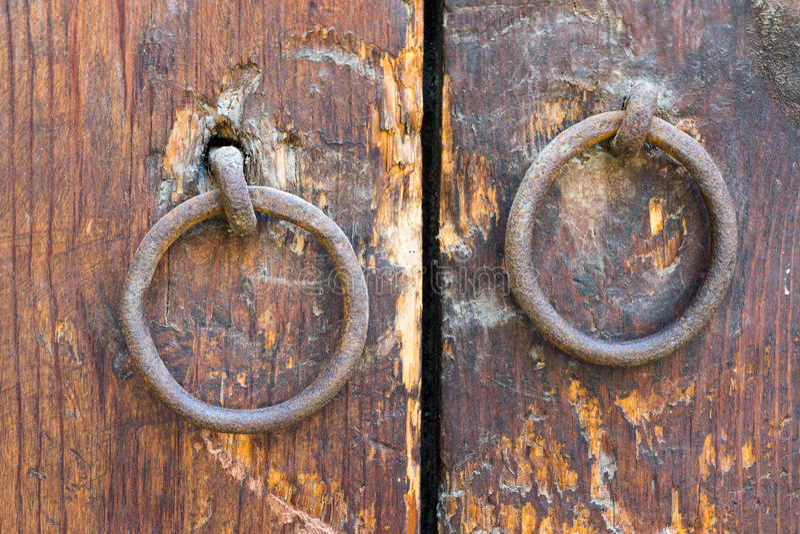 在一个老木门的两个生锈的铁圆环门把手 库存图片