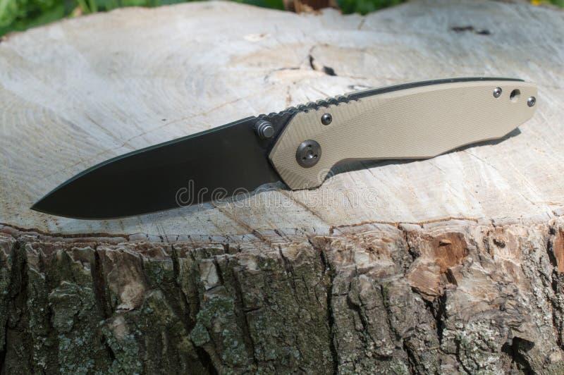 在一个老树桩的折叠的刀子 免版税图库摄影