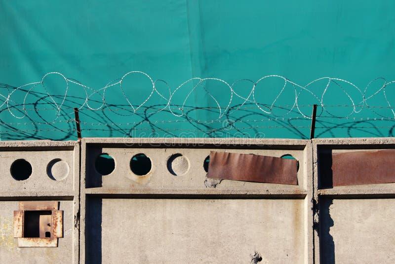 在一个老混凝土墙上的铁丝网防护装置一个对象防御一个绿色遮篷 图库摄影