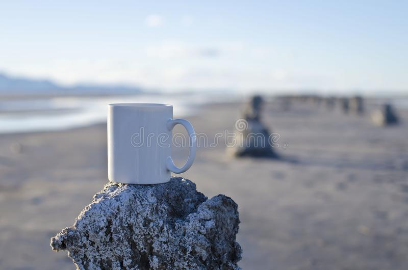 在一个老码头的长的空白的加奶咖啡杯子 免版税库存照片