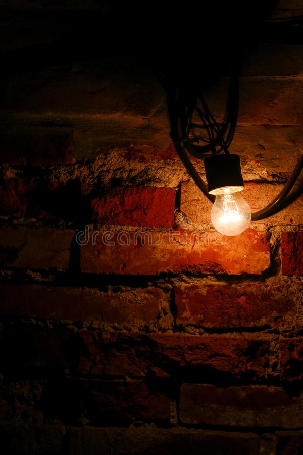 在一个老砖墙旁边的明亮的电灯泡 库存图片