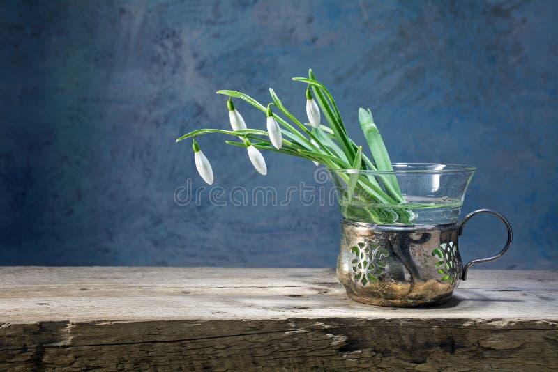 在一个老花瓶的Snowdrops银和玻璃在一土气木 免版税库存图片