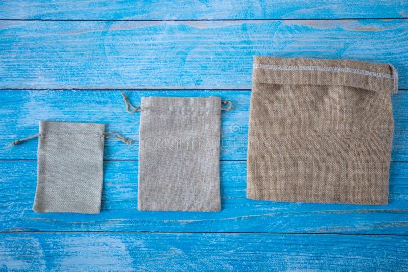 在一个老蓝色木地板、袋子自然godds和礼物的,背景空间文本的和设计安置的空的粗麻布大袋 免版税库存照片