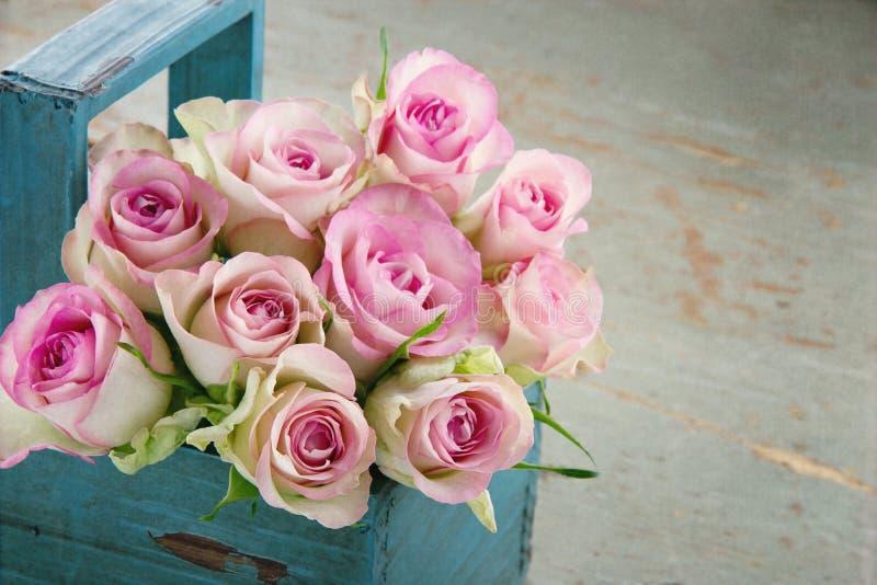 在一个老蓝色木篮子的玫瑰 免版税库存照片