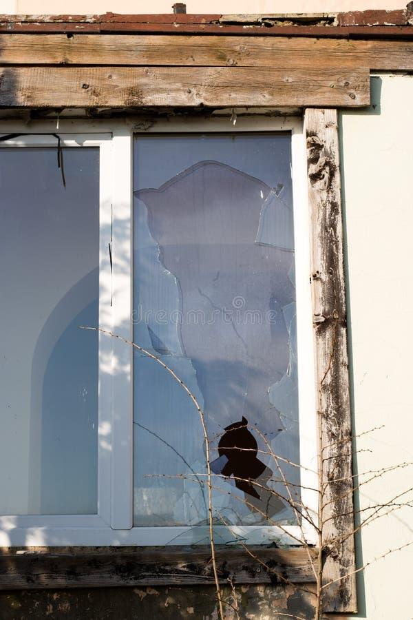 在一个老被放弃的大厦的一个残破的窗口 在Th的残破的玻璃 免版税库存照片