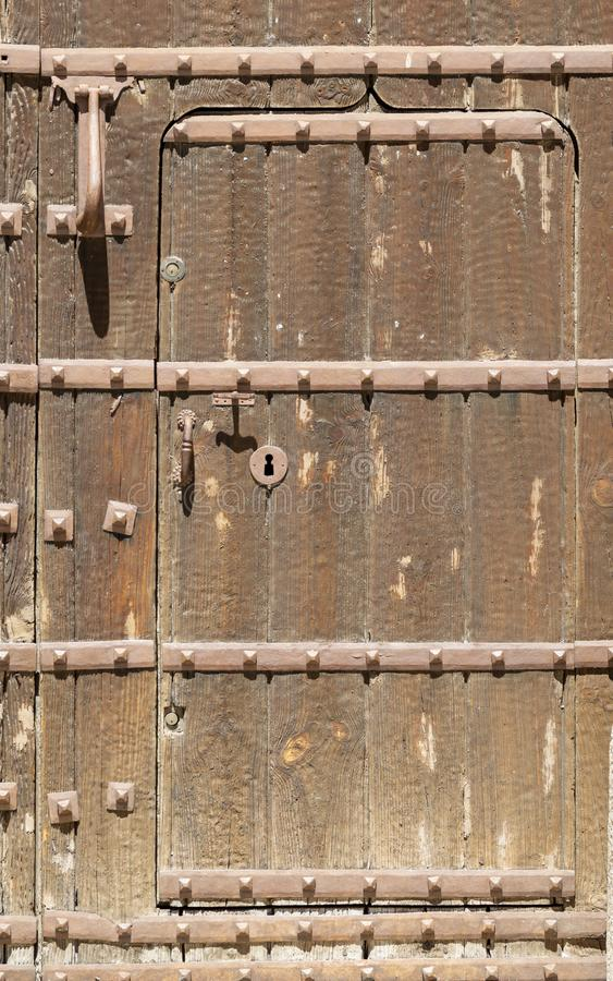 在一个老被镶板的木门的匙孔与古色古香的门把手;生锈和风化 免版税库存照片