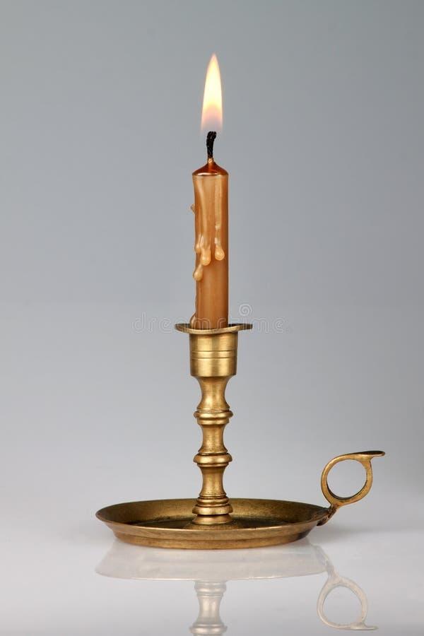 在一个老黄铜烛台的被点燃的蜡烛。 库存照片