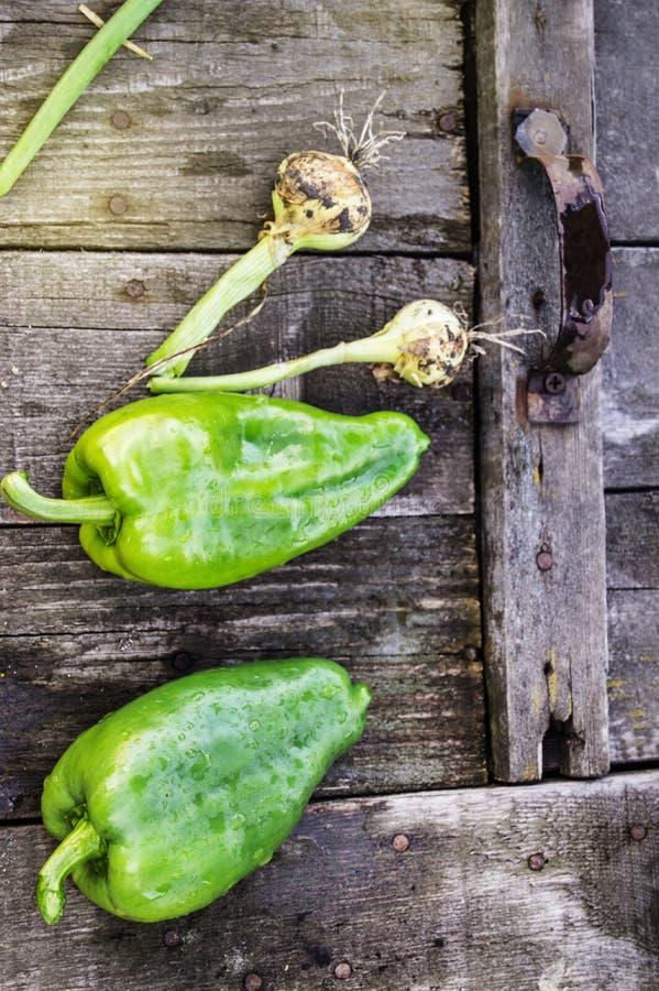 在一个老黑暗的木板、水下落在有机新鲜蔬菜,素食和营养的两个绿色未加工的甜椒 库存照片