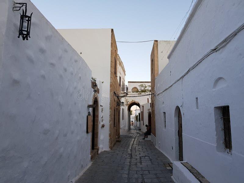 在一个老greec镇的街道上的白色老房子在日落晚上 免版税图库摄影