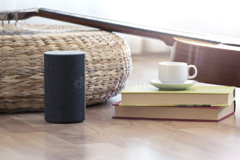 在一个聪明的家庭客厅的一个木地板上的个人助手扩音器 其次,吉他和有些书和一杯咖啡 免版税库存图片