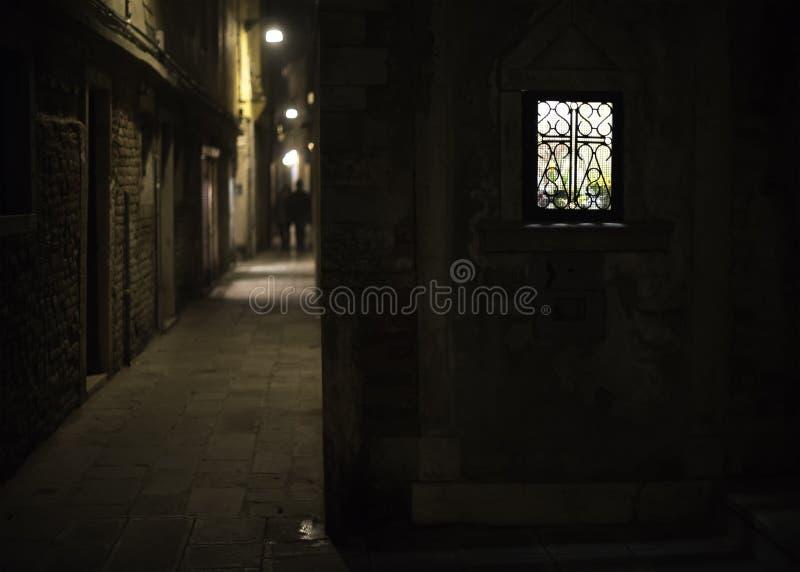 在一个胡同的明亮地被点燃的窗口在晚上 库存照片