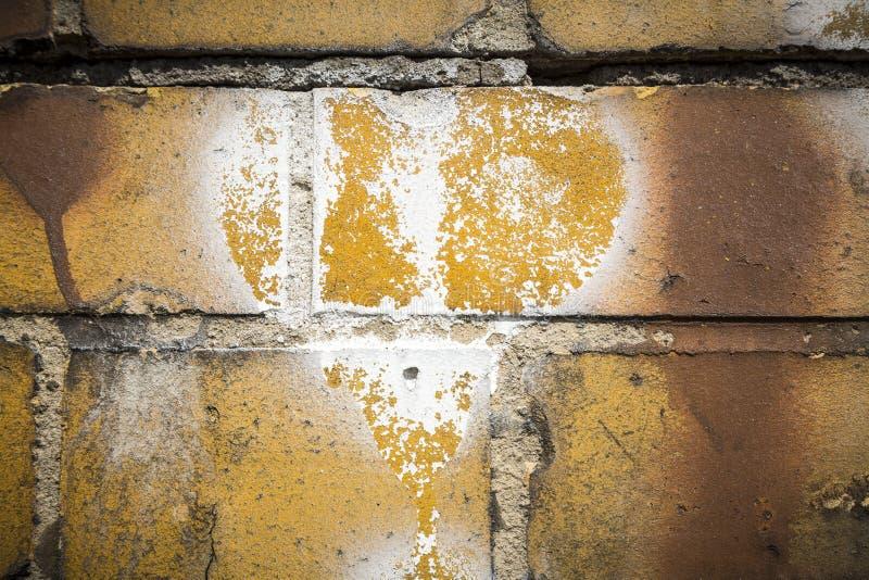 在一个脏的黄色砖墙上的心脏标志 库存照片