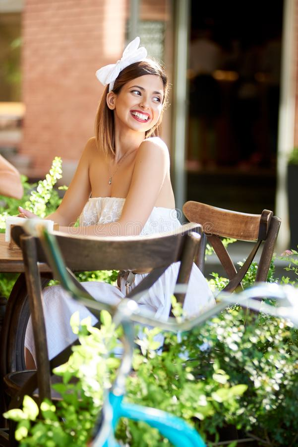 在一个舒适咖啡馆的微笑的女性开会在一个晴天 库存图片