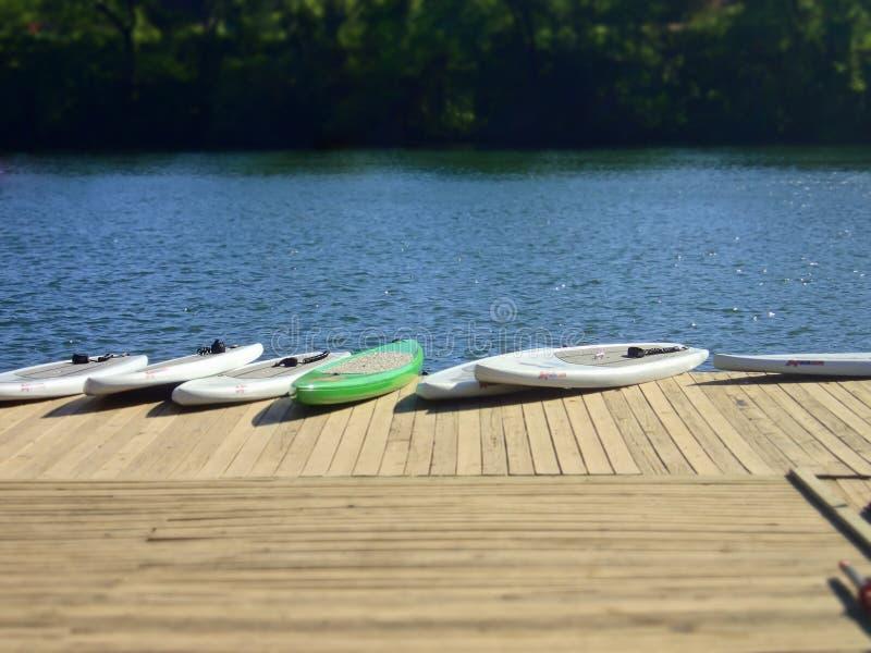 在一个船坞的直立的Paddleboards湖的 图库摄影