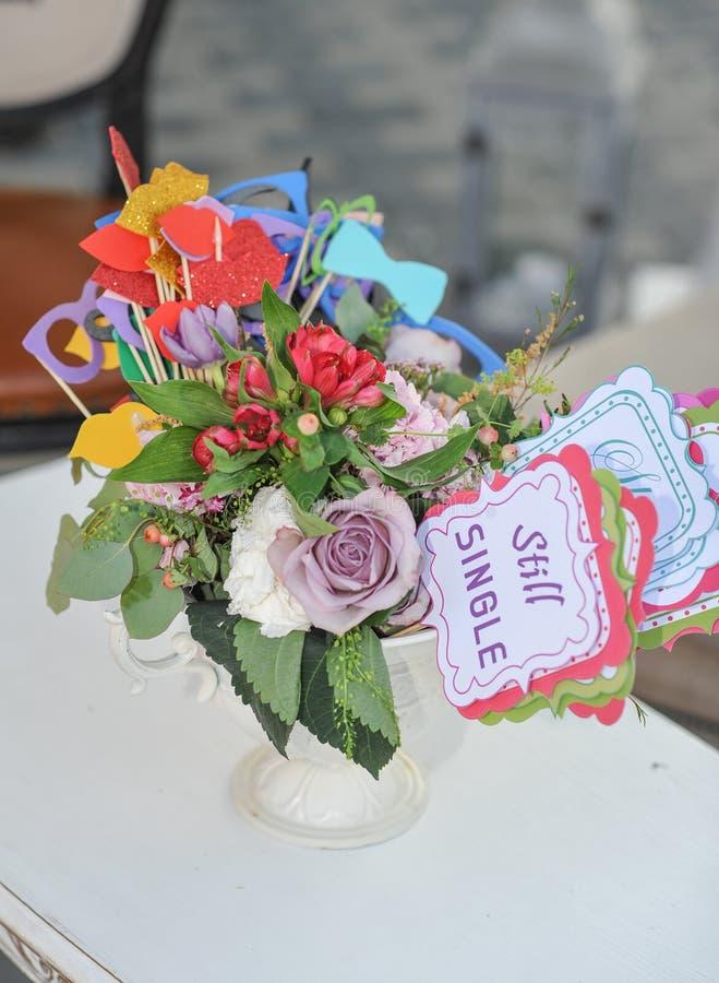 在一个花瓶在桌上和标记的多彩多姿的鲜花花束和纸装饰与词仍然选拔 重点玻璃表婚礼 库存图片
