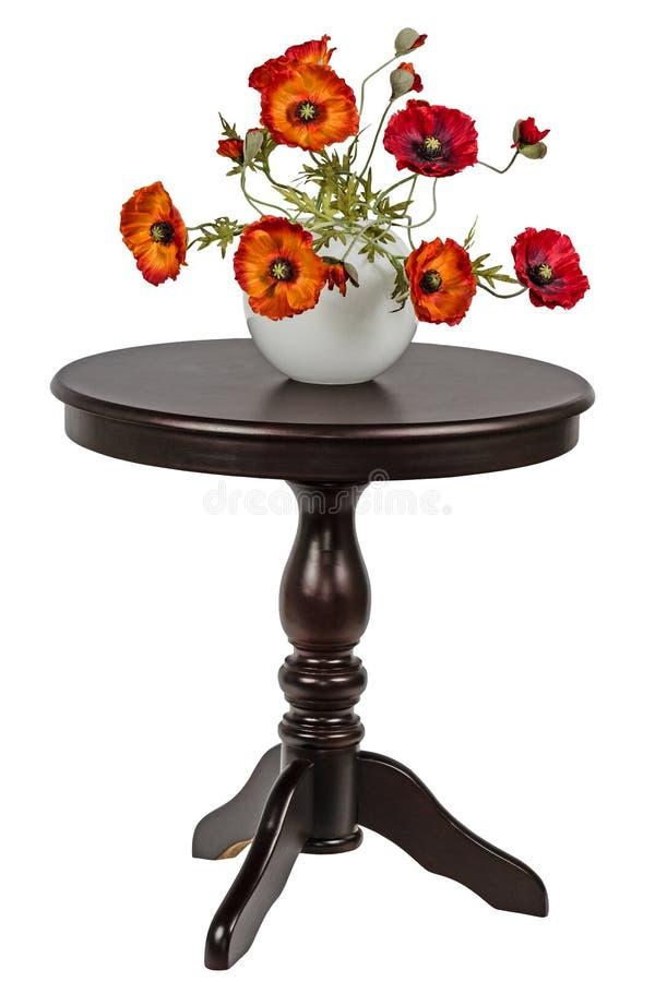 在一个花瓶的人为鸦片在圆桌上 免版税图库摄影