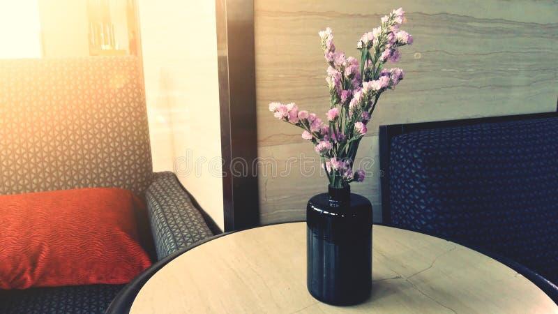 在一个花瓶的小桃红色花在木台式 免版税库存图片