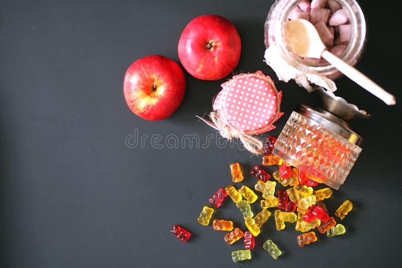 在一个花瓶的橘子果酱在桌上 在一个碗的甜点在黑ba 库存图片