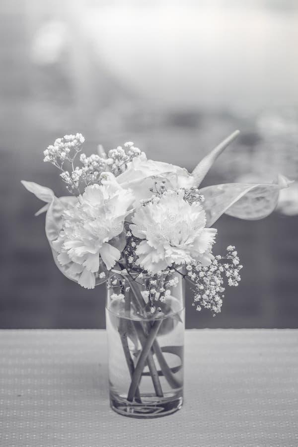 在一个花瓶的白花在与黑色和whi的咖啡桌上 图库摄影