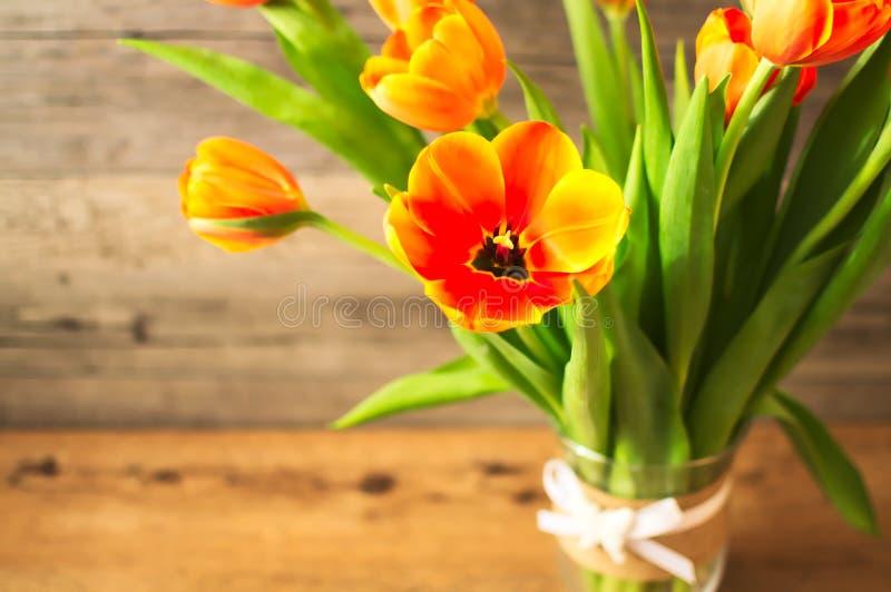 在一个花瓶的美丽的橙色郁金香在棕色木背景 可爱的夫人的一种理想地说春天心情 免版税库存图片