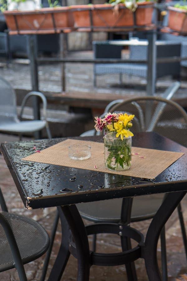在一个花瓶的花束在与下落的一张桌上在一下雨天 免版税库存照片