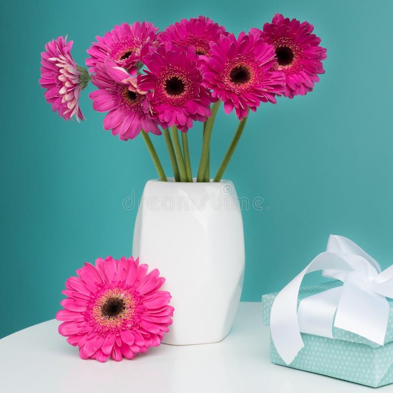 在一个花瓶的黑暗的桃红色大丁草在与美好的礼物的一张桌上 愉快的母亲` s天,妇女` s天,华伦泰` s天或生日 库存照片