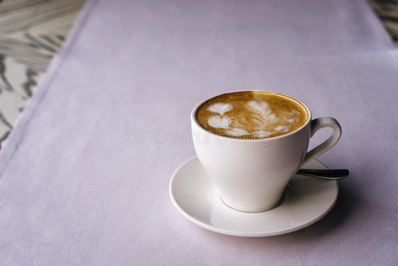 在一个茶碟的白色杯子有热奶咖啡和美丽的心形的牛奶泡沫的 库存图片
