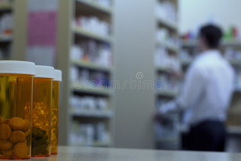 在一个药房柜台的药瓶与药剂师在背景中 免版税库存照片