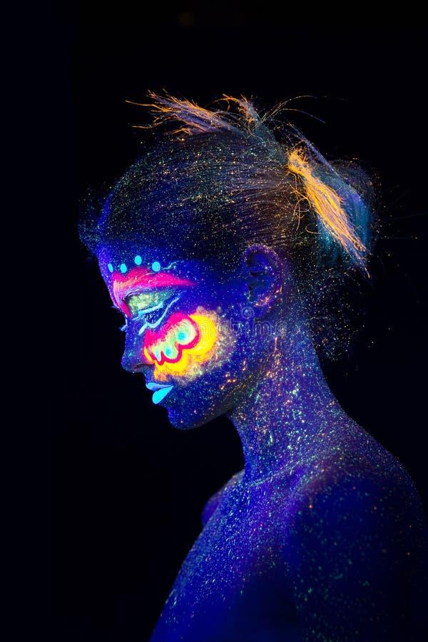 在一个蓝色外籍人女孩的档案的画象有蝴蝶翼的样式的在她的面颊的 紫外构成,眼睛关闭了 免版税库存照片